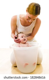 Adult mother wearing bright casual clothes, she kneels on the floor and bathes her newborn baby in the bath bucket. Carefully, she keeps the baby's head. Isolated against white background.