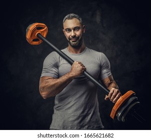Adult muscular caucasian man coach posing for a photoshoot in a dark studio under the spotlight wearing grey sportswear, showing his muscles and holding a barbell