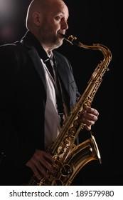 Adult musician playing tenor saxophone eyes open, dark background