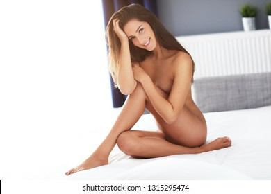 Adult naked woman lying in bed in the morning