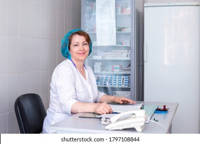 adult nurse in a medical blue cap sits at a table in the vaccination room. Workplace in a polyclinic in Russia. Coronavirus vaccinations.
