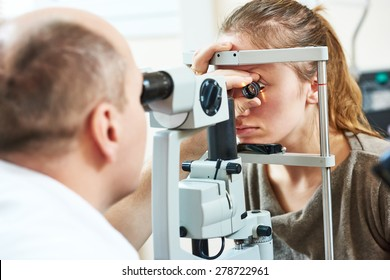 Adult optometry. male optometrist optician doctor examines eyesight of young woman patient in eye ophthalmological clinic