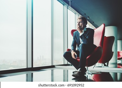 Adult pensive and anxious businessman in blue formal suit is sitting on red armchair in luxury office interior near window and recapitulating recent work meeting with copy space zone for advertising