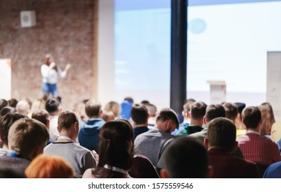 Adult people at conference listen to woman speaker providing lecture on scene in big conference hall. Business and Entrepreneurship concept. Audience at the conference hall.