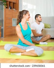 Adult people doing yoga on mats indoor