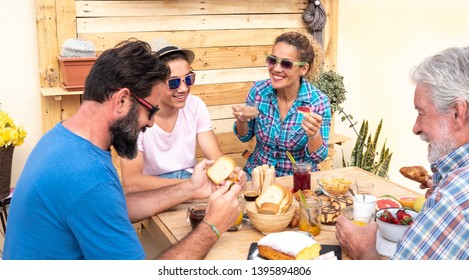 Adult people enjoy the breakfast together. Outdoor in the terrace. Family three generations. Food on the table with fresh fruit and homemade cake.