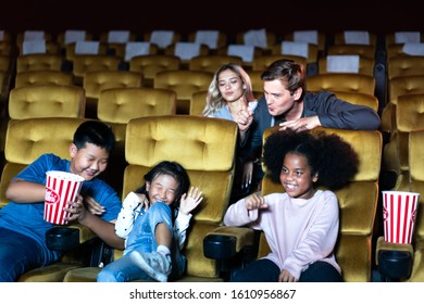 Adult people man has angry and annoyed a loud of kids group during watching movie in cinema theater. He use a shh gesture for quiet please.