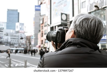 Adult people photographer journalist travelers take photo billboard building or businesson shopping neon street of shinjuku area at Tokyo, Japan