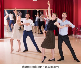Adult people practicing passionate samba in dance class