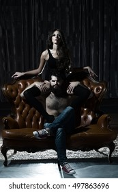 Adult people, relations. Young couple with sexy girl and handsome man on sofa.