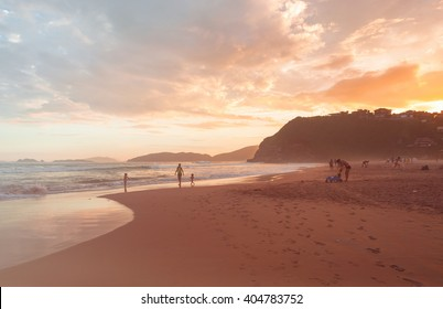 Adult people walking on the beach on sunny day  Men women and children enjoying a summer day in twilight on coastline, image for travel business concept, blog, magazine. Toned filter lens flare effect