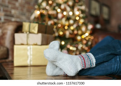 Adult person sitting on a sofa dressed Christmas socks. Golden lights on Christmas tree on the background. Waiting for Christmas concept