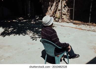 An adult person with a trilby hat sitting on a plastic chair outdoors on a sunny day
