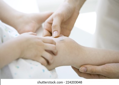 Adult placing adhesive bandage on child's knee, cropped view