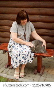 An adult plump woman sits on a bench near a log house and strokes a gray cat