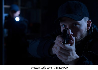 Adult police officer pointing gun at criminal