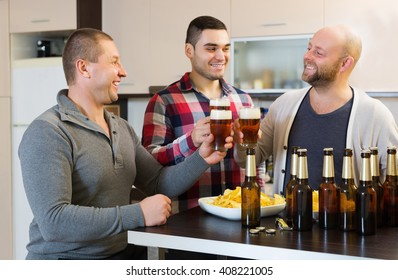 Adult positive men relaxing with beer and smiling at home
