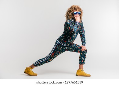 Adult positive smiling funky man with curly hair style in suglasses and vintage clothes posing on white studio background. Funny portrait of stylish male person. 80s fashion. Unusual eccentric guy
