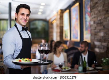 Adult positive waiter standing with tray with glass and salad in restaurant
