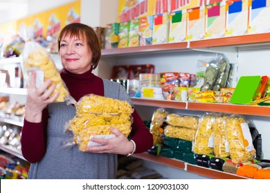 Adult positive woman buyer choosing packaging of pasta in the food store