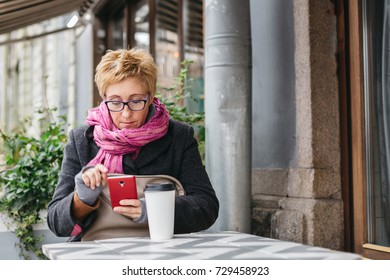 Adult pretty woman browsing smartphone in outside cafe.