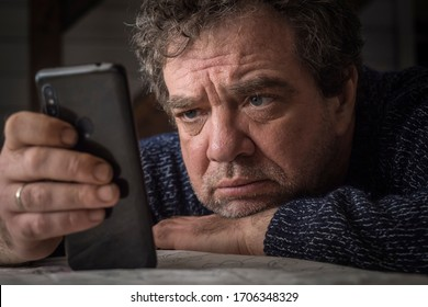 Adult sad man with smartphone at home in quarantine isolation