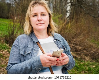 An adult sad woman with a smartphone in the forest. Real people
