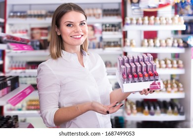 Adult salesgirl offering fashionable colors of lipstick at cosmetics store