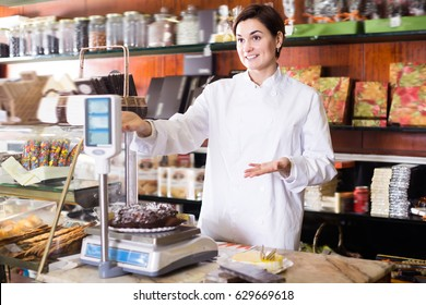 Adult seller weighing festive chocolate cake in confectionery