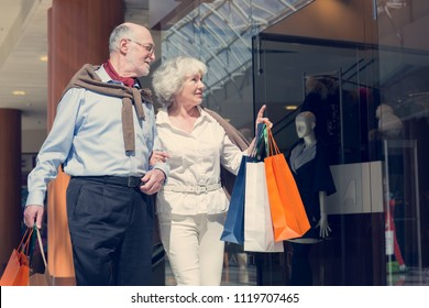 Adult senior couple with purchases in bags at shopping mall
