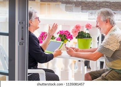 adult senior couple use laptop outdoor leisure activity at the terrace at home. smile and enjoy the nice weather and the retired life staying together all the days without work. technology stay young
