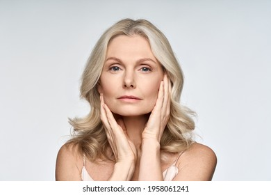 Adult senior older woman touching her perfect skin. Beautiful portrait mid 50s aged woman advertising facial anti age lift products salon care tighten skin isolated on white looking at camera.