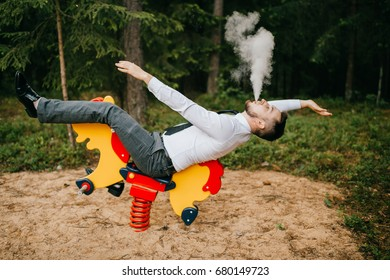 Adult serious man in business clothes riding children metal horse attraction with spring on playground. Odd person blows out clouds of thick smoke. Strange posing with arms apart. Weird behavior.