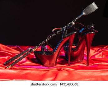Adult sex games. Kinky lifestyle. Spank and a pair of black high-heeled shoes on the red linen. Bdsm outfit - Image