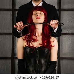 Adult sex games. A man holds a spank near the neck of a red-haired girl in a leather corset. Bdsm outfit