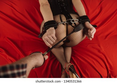 Adult sex games. Submissive girl in bondage and man's hand with spanking prepare for punishment. - Image