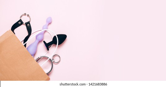 Adult sex toys and accessories purchases on pink background. Anal dildo, butt plug in paper bag. Top view, flat lay.