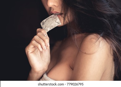 Adult sexy woman prepare a condom for use in safe sex to protect from disease aids and contraception from pregnant accidentally