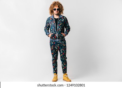 Adult shylish man in fashionable tracksuit with flowers pattern, yellow sneakers standing with hands in pockets on white background. Guy with curly hair. Awesome confident male in sunglasses portrait