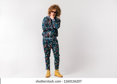 Adult shylish man in fashionable tracksuit with flowers pattern, yellow sneakers posing on white background. Funky man stroking shaved beard. Awesome confident funky male in sunglasses portrait