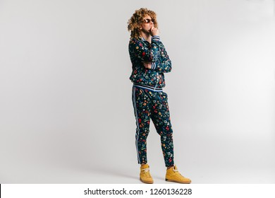 Adult shylish man in fashionable vintage style tracksuit and sneakers posing on white background. Funky man stroking  beard. Awesome confident male in sunglasses portrait. 80s fashion. Serious person.