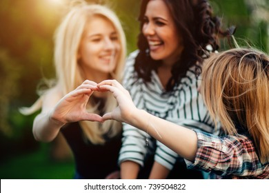 Adult sisters in a park at wonderful day making heart gesture