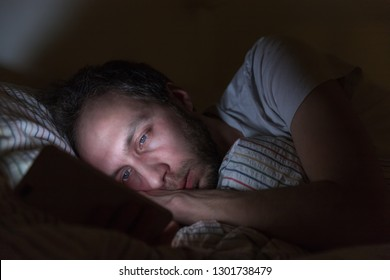 Adult sleepy male awake late at night in bed surfing in web, chatting and flirting/ sleepy tired, social media addiction, dependency on a cell phone, negative effect on the eyes, sleeplessness concept