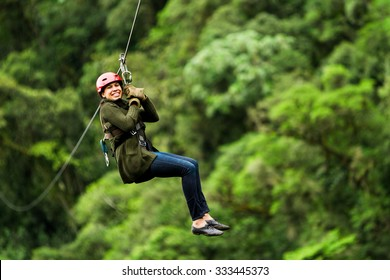 Adult Slim Afro Woman On Zip Line In Ecuadorian Rainforest Nearby Banos De Agua Santa