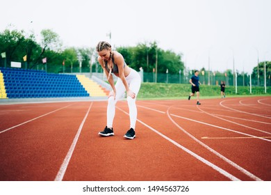 Adult slim female in sportive wear standing on track leaning on knees and recovering breath after exercising against stadium seats looking down
