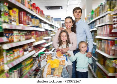 Adult smiling family with two daughters shopping in local supermarket