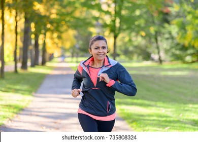 Adult smiling woman running in park on sunny day