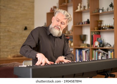 adult solid gray-haired man with a stylish beard plays the electronic piano at home in his spare time