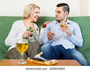 Adult son congratulating elderly mother and proposing a toast