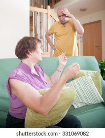 Adult son and elderly mother during  quarrel  at home.